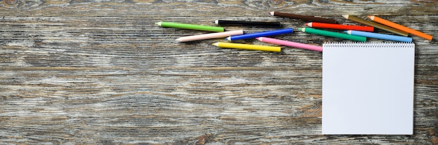 空白のノートブックと木製のテーブルにカラフルな鉛筆のセット。用紙の背景。