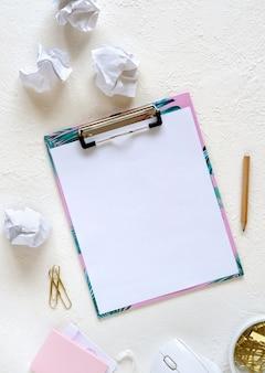 空白のノートブックと白い背景の上の文房具。デザインのモックアップ