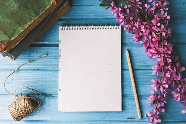 Пустой блокнот и полевые цветы на синем деревянном фоне. концепция цветы весны,