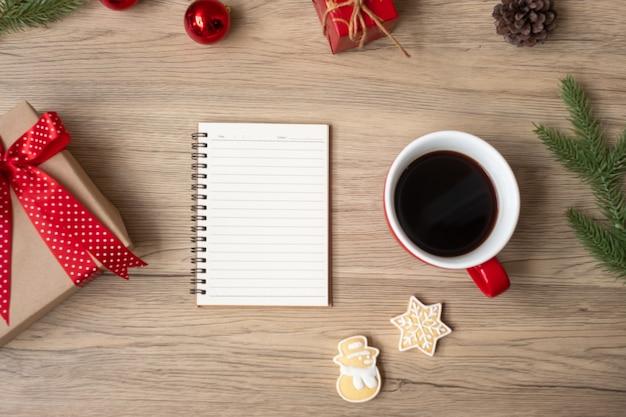 空白のノートブック、黒いコーヒーカップ、木製のテーブルにクリスマスクッキーとペン、上面図とコピースペース。クリスマス、明けましておめでとう、目標、決議、やることリスト、戦略と計画の概念