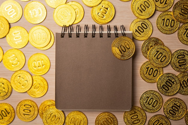 Blank notebook or calendar with golden coins, top view