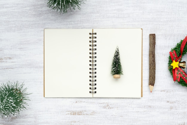 Blank  notebook and christmas ornaments on white wood