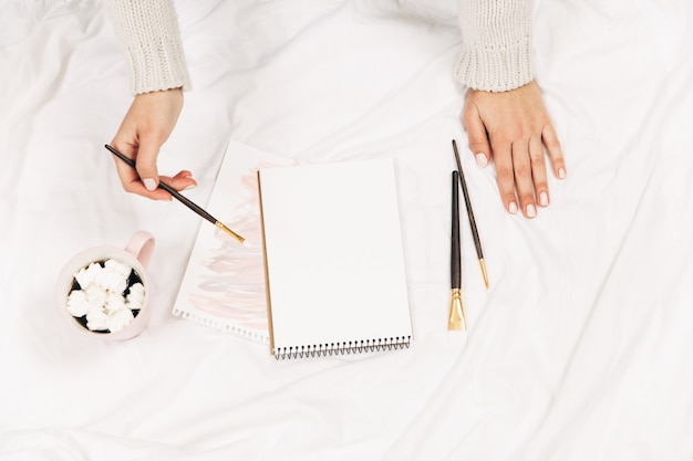 Blank notebook, coffee, watercolor brushes and coffee with marshmallows in woman's hands, top view
