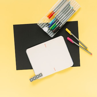 Blank notebook and colorful felt-tip pens on black and yellow card paper background