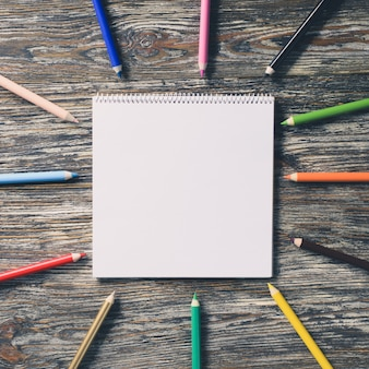 Blank notebook and colorful pencils on the wooden table. paper background.