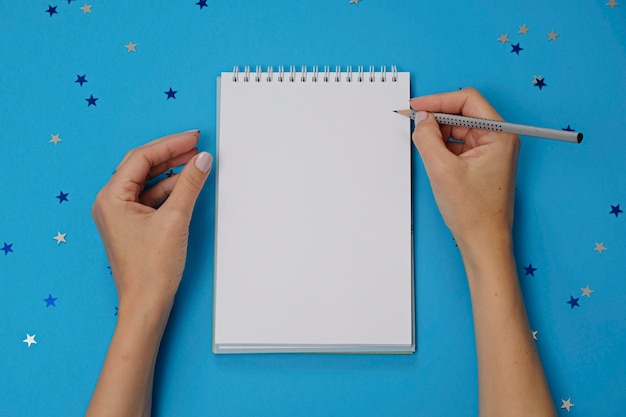 Blank notebook and female hands with pencil