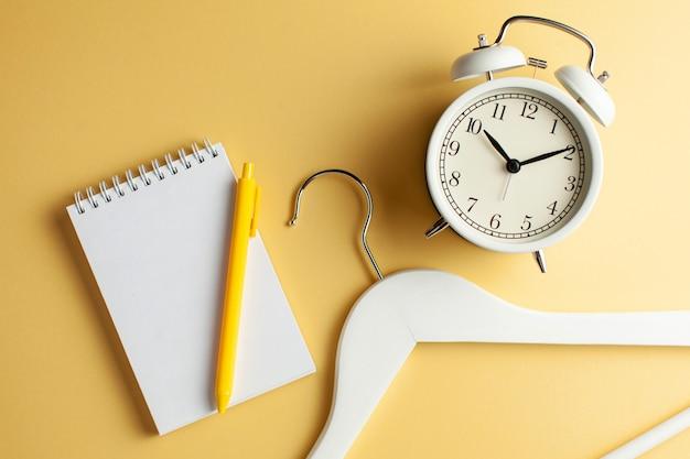 Пустой блокнот для текста, вешалка для одежды и белые часы на желтом фоне