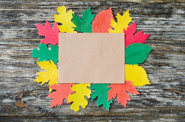 Blank notebook in a frame of autumn paper leaves on vintage wood