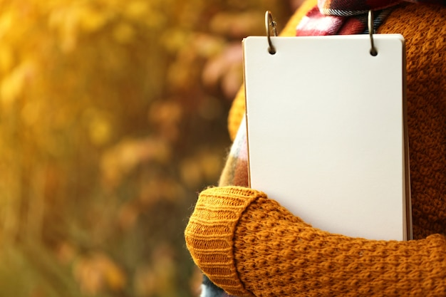 Blank notebook in hands on autumn blurred in sunset rays background