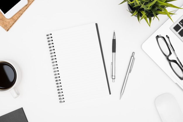 Blank notebook is on top of white office desk table with laptop, coffee cup and office supplies.