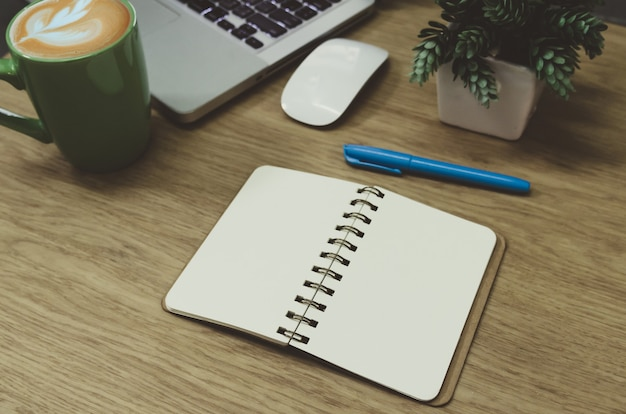Пустой блокнот, лежащий на деревянном столе и зеленая кофейная кружка на компьютере