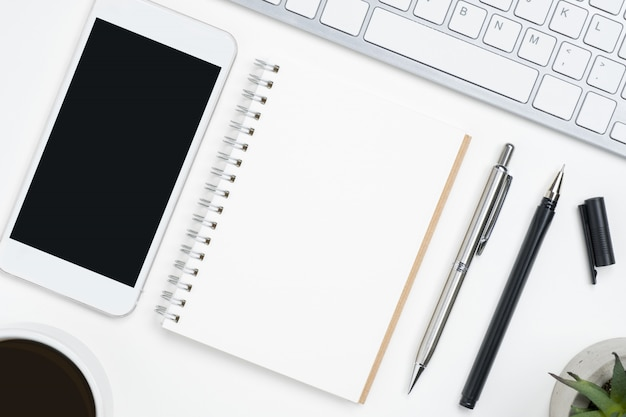 Blank notebook and mobile phone with blank mockup screen are on top of white office desk table.