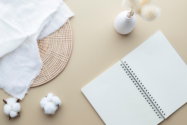 Blank notebook mockup on a beige background, cotton flower, reeds grass in a vase, white blanket, rattan basket, flat lay, top view, copy space