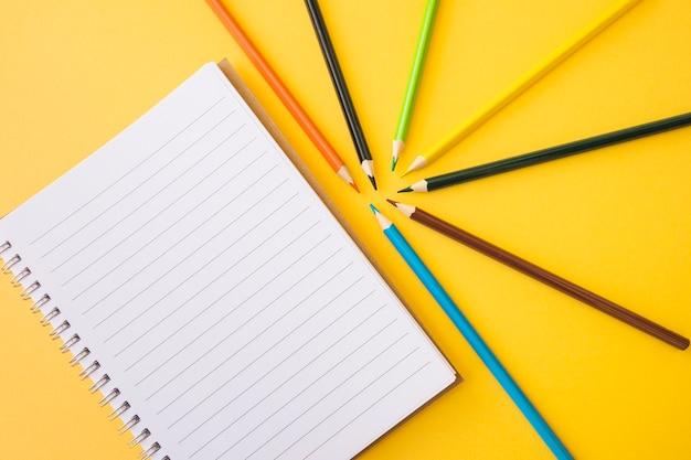 Пустой ноутбук рядом с карандашами