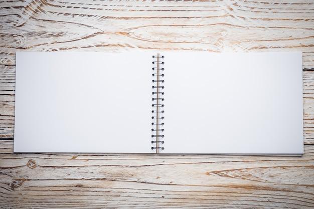 木製の背景の空白のノートブック