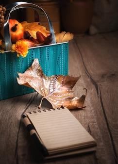秋の装飾と木製のテーブルの上の空白のノートブック