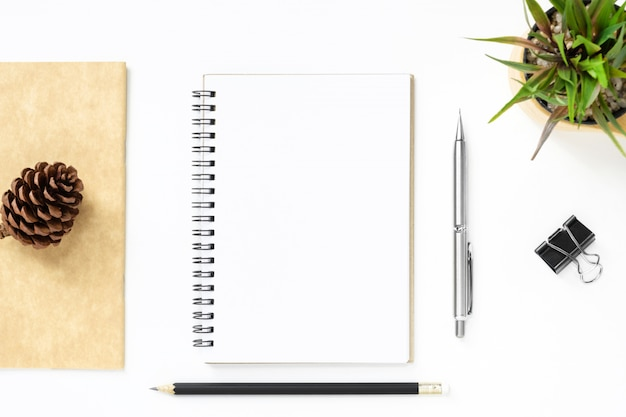 Blank notebook page is on top of white office desk table with pen