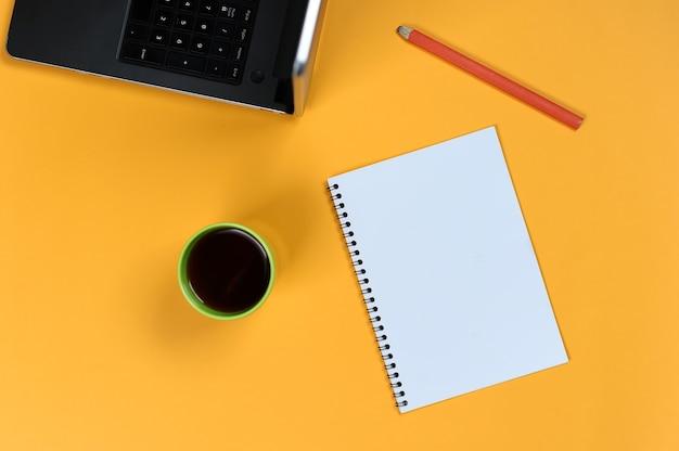 Пустая страница ноутбука, ноутбук, кофейная чашка и карандаш. пустой блокнот для идей и вдохновения на цветном фоне