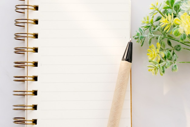 Blank notebook paper and pen on white marble background, with copy space for text, top view