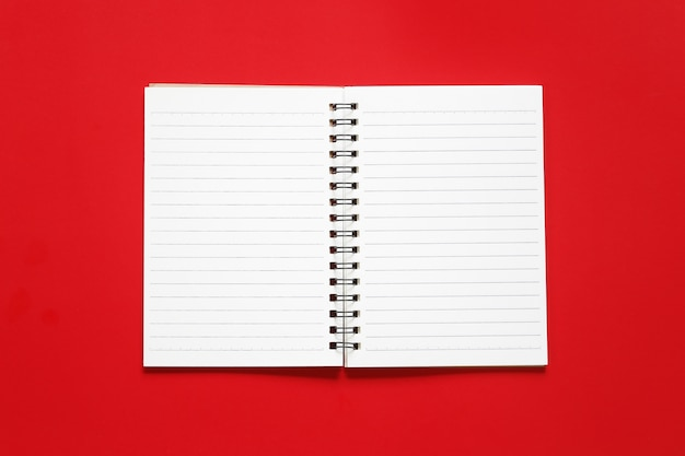 Blank notebook paper on a red art paper background.