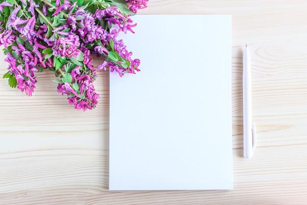 Пустая ручка для ноутбука и розовые цветы с зелеными листьями на деревянном фоне, вид сверху