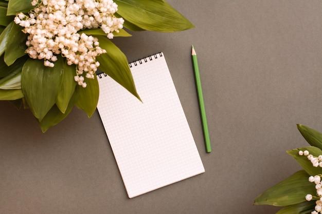空白のノート、鉛筆、緑のテーブルの上の谷のユリの花束。上面図。計画、目標設定、ウィッシュリスト。春のアップデート