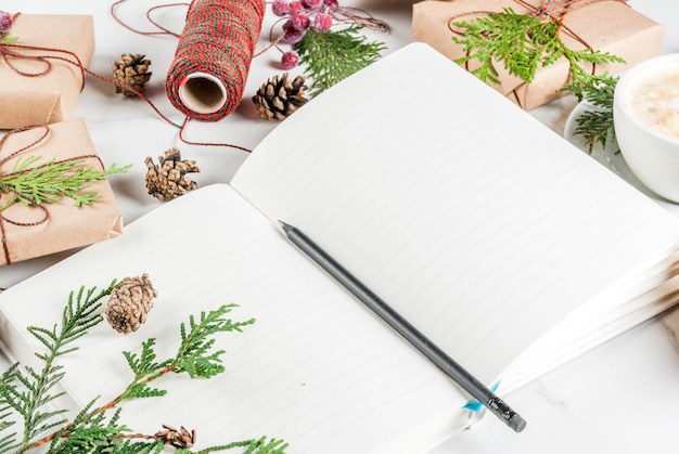Blank notebook and pencil for wishes, to do list, coffee mug, christmas gift or present box, decorated with christmas tree branches, pine cones, red berries, on white marble table, copy space