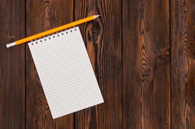 Blank notebook and pencil on a wooden surface