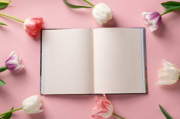Blank notebook on a pink background with a frame of beautiful flowers. planer concept. space for text. flat lay, top view