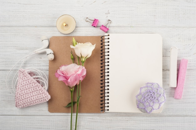Blank notebook, pink crochet holdel, earphones