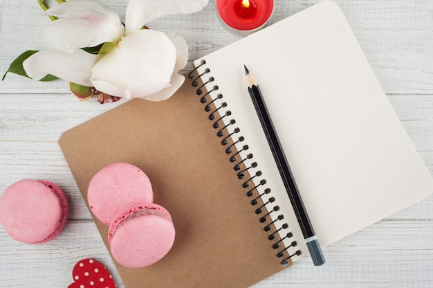 Blank notebook, pink macaroons, lit candle