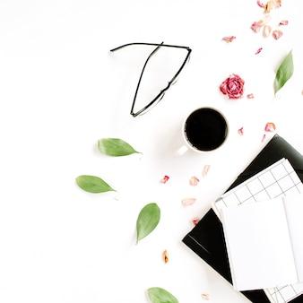 空白的笔记本,红色玫瑰芽,玻璃,叶子,在白色表面上的咖啡