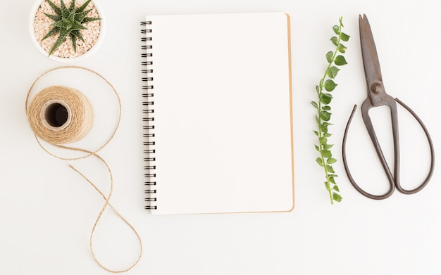 Blank notebook and scissors on white