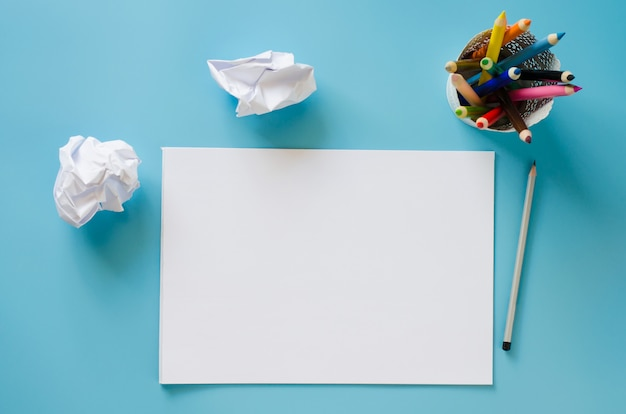 Blank notebook, set of colorful pencils and crumpled up papers . paper background.