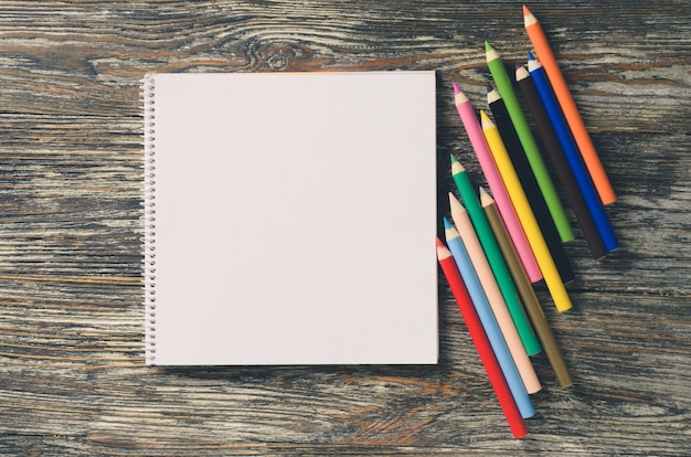 Blank notebook and set of colorful pencils on the wooden table. paper background.