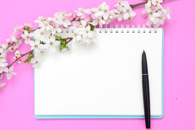 Blank notebook sheet with pen and flowering branches with white flowers on a pink background. spring mock up for your texts