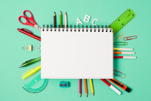 Blank notebook surrounded by stationery school supplies