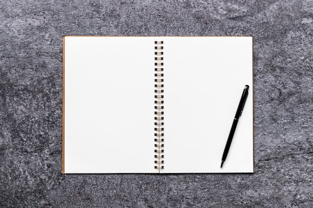 Blank notebook on table gray stone with black pen