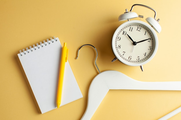 Blank notebook for text, a clothes hanger and a white clock on a yellow background.