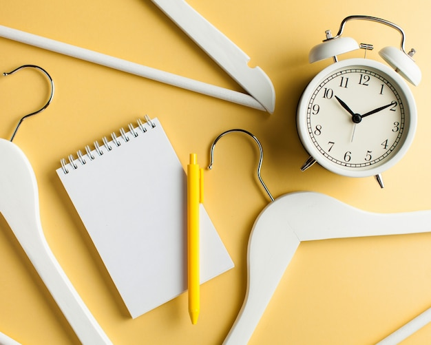 Blank notebook for text, a clothes hanger and a white clock on a yellow background