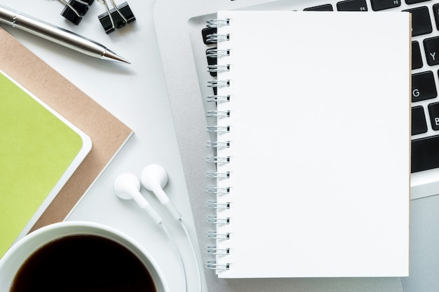 Blank notebook on top of modern white office desk table. top view, flat lay.