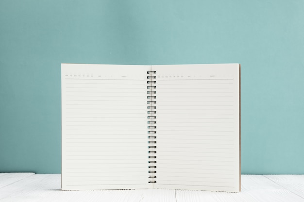 Blank notebook on white wood table front green wall background