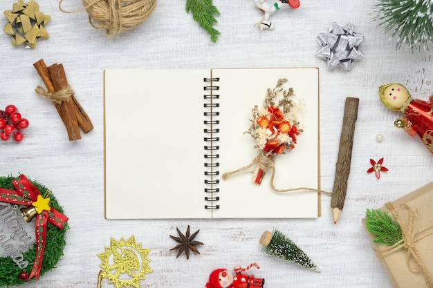 Blank notebook on white wood with christmas ornaments.