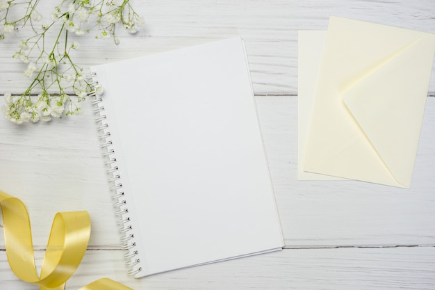 Blank notebook on white wooden background. flat lay composition with free space for text.