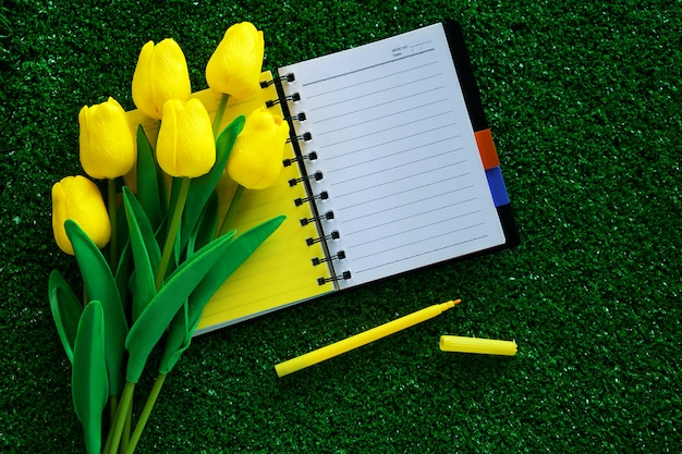 Blank notebook with artificial yellow tulips and a pen on green grass for workspace, nature decoration and springtime concept