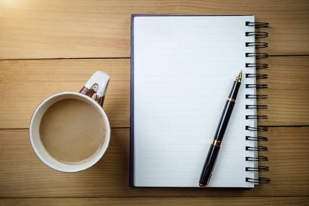 Blank notebook with blank pages and with glasses next to cup of coffee on wooden table.