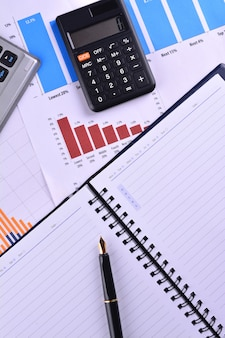 Blank notebook with calculator, keyboard and fountain pen on graphs, charts and business table. the workplace of business people