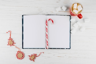 Blank notebook with candy cane on table