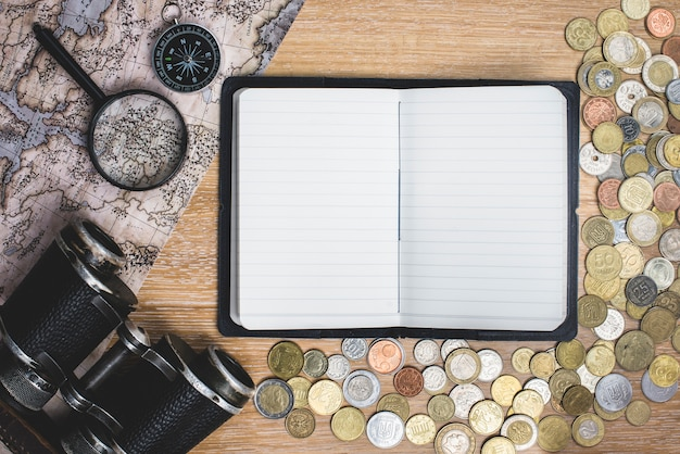 Blank notebook with coins and travel objects
