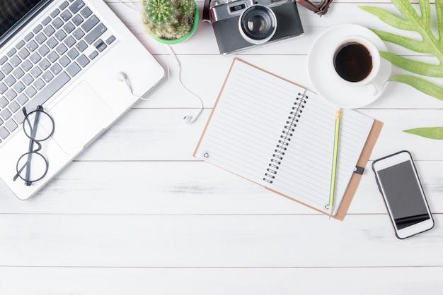 コンピュータ、コーヒー、ヴィンテージカメラ付きの空のノートブック